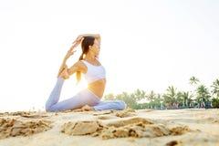 Übendes Yoga der kaukasischen Frau an der Küste von tropischem Ozean stockfotos
