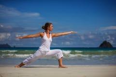 Übendes Yoga der kaukasischen Frau an der Küste von tropischem Ozean Stockfoto