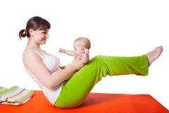 Übendes Yoga der Mutter der jungen Frau mit Baby Stockbild