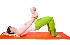 Übendes Yoga der Mutter der jungen Frau mit Baby Lizenzfreie Stockfotos