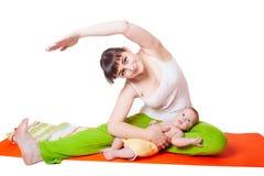 Übendes Yoga der Mutter der jungen Frau mit Baby Stockfotos