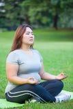 Übendes Yoga der Plusgrößenfrau Stockbild