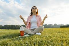 Übendes Yoga der reifen Frau, das auf dem Gras sitzt Frau im Park mit Sommergetränk, Buch, Rest und Meditation, goldene Stunde stockbilder