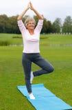 Übendes Yoga der reifen Frau im Park Lizenzfreies Stockfoto