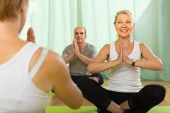 Übendes Yoga der reifen Paare mit Lehrer Stockbilder