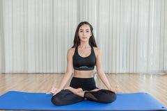 Übendes Yoga der schönen asiatischen Frau und gymnastisch auf blauer Matte lizenzfreie stockfotografie