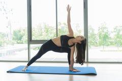 Übendes Yoga der schönen asiatischen Frau und gymnastisch auf blauer Matte an der Turnhalle stockbilder
