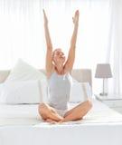 Übendes Yoga der schönen Frau auf ihrem Bett Lizenzfreie Stockfotos