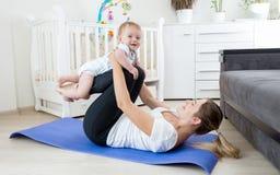 Übendes Yoga der schönen Mutter mit ihrem Baby Lizenzfreies Stockbild