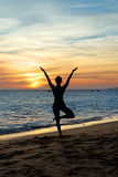 Übendes Yoga der Schattenbildfrau auf Sonnenuntergang Stockfotografie