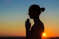 Übendes Yoga der sportlichen Frau bei dem Sonnenuntergang, Handgruß namaste machend Stockfotografie