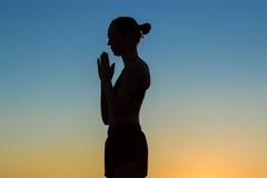 Übendes Yoga der sportlichen Frau bei dem Sonnenuntergang, Handgruß namaste machend Lizenzfreies Stockfoto