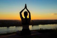 Übendes Yoga der sportlichen Frau bei Sonnenuntergang - sonnen Sie Gruß Stockbild