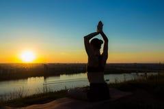 Übendes Yoga der sportlichen Frau bei Sonnenuntergang - sonnen Sie Gruß Stockbilder