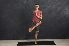 Übendes Yoga des jungen flexiblen Mannes an der Turnhalle Lizenzfreies Stockbild
