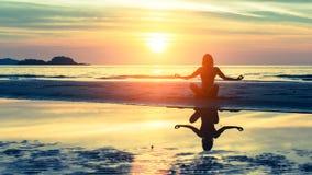 Übendes Yoga des jungen gesunden Frauenschattenbildes lizenzfreie stockfotografie