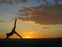 Übendes Yoga des Mädchens auf einem Hintergrund von Bergen und von Sonnenuntergang stockbild