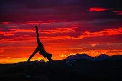 Übendes Yoga des Mädchens auf einem Hintergrund von Bergen und von Sonnenuntergang stockfotos
