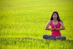 Übendes Yoga des Mädchens, sitzend auf dem Paddygebiet Lizenzfreie Stockbilder