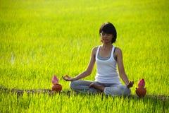 Übendes Yoga des Mädchens, sitzend mit Lotosblume Lizenzfreies Stockfoto