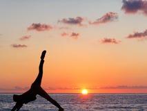 Übendes Yoga des Mädchens vor dem hintergrund des Ozeans und der Sonne lizenzfreie stockbilder