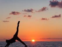 Übendes Yoga des Mädchens vor dem hintergrund des Ozeans und der Sonne stockfotos