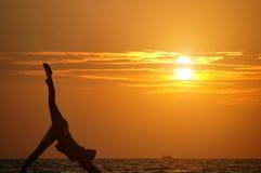 Übendes Yoga des Mädchens vor dem hintergrund des Ozeans und der Sonne lizenzfreies stockbild