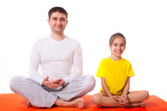 Übendes Yoga des Vatis mit der Tochter lokalisiert Lizenzfreies Stockbild