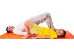 Übendes Yoga des Vatis mit der Tochter lokalisiert Lizenzfreie Stockbilder