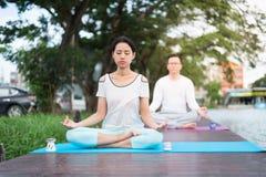 Übendes Yoga und Meditation der Frau auf Matte nahe Lagune mit Freund lizenzfreies stockbild