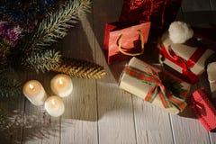 Über Ansicht über das neue Jahr wickelte Geschenke, glühende Kerzen und Teil des Weihnachtsbaums auf dem alten Holztisch ein Stockbild