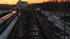 Über Ansicht des Güterzugs mit den Flachwagen, die durch Bahnhof bei Sonnenuntergang überschreiten stock video