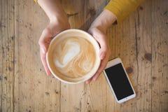 Über Ansicht von den weiblichen Händen, die heißen Tasse Kaffee halten und mit intelligentem Telefon mit auf Holztisch stockbilder