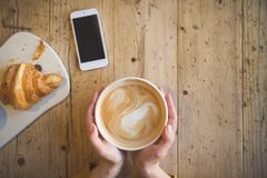 Über Ansicht von den weiblichen Händen, die heißen Tasse Kaffee halten und mit intelligentem Telefon mit auf Holztisch Kaffeepaus Lizenzfreies Stockfoto
