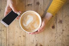 Über Ansicht von den weiblichen Händen, die heißen Tasse Kaffee halten und mit intelligentem Telefon mit auf Holztisch Kaffeepaus lizenzfreie stockbilder