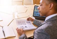 Über dem Schulterbild des Geschäftsmannes Dokument mit Grafiken verwahrend Lizenzfreie Stockfotografie