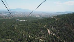 Über den Bäumen Drahtseilbahn auf Berg Parnitha: Ansicht über Athen, Griechenland Lizenzfreies Stockfoto