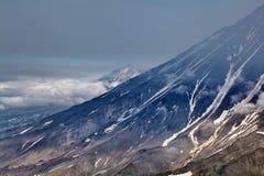 Über den einzigen Vulkanen der Wolken Vulkane von Kamchatka faszinieren Ihre R?tselhaftigkeit zieht viele Touristen an lizenzfreie stockbilder
