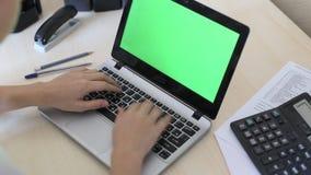 Über der Schulter schoss von einer Frau, die auf einem Laptop mit einem Schlüssel-grünen Schirm schreibt stock video