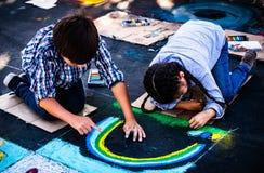 Über die Arte-Kinderkünstler, die Kreidekunst auf Straßen schaffen stockbilder