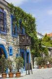 Über efeubewachsenem, altem Steingebäude mit blauen Streifen Stockfotografie