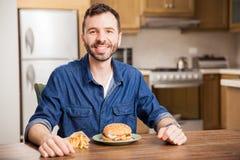 Über einen Hamburger zu Hause essen stockbild
