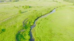 Über einen kleinen Fluss fliegen, ein Strom, der die Floodplaingrünwiesen eines ländlichen Platzes im Sommer durchfließt stock video