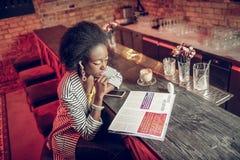 Über Foto der afroen-amerikanisch fantastischen Frau, die beteiligt Zeitschrift betrachtet stockbild