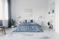 Über großem bequemem Bett im Luxus-New- Yorkartschlafzimmer schmerzen, wirkliches Foto stockfoto