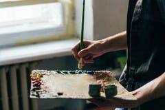 Über vom Fenster hält der Künstler eine Palette mit Farben und einer Bürste und wird auf Segeltuch malen Stockfotos