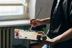 Über vom Fenster hält der Künstler eine Palette mit Farben und einer Bürste und wird auf Segeltuch malen Stockfotografie