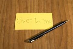Über zu Ihnen handwrite auf einem gelben Papier mit einem Stift auf einem teble lizenzfreie stockbilder