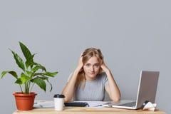 Überarbeitete blonde Frau hat Kopfschmerzen, sitzt am Arbeitsplatz, umgeben mit Papieren und Laptop-Computer und ist mit dem Vorb Lizenzfreie Stockbilder