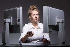 Überarbeitete Frau, die an den Computern sitzt Lizenzfreies Stockbild